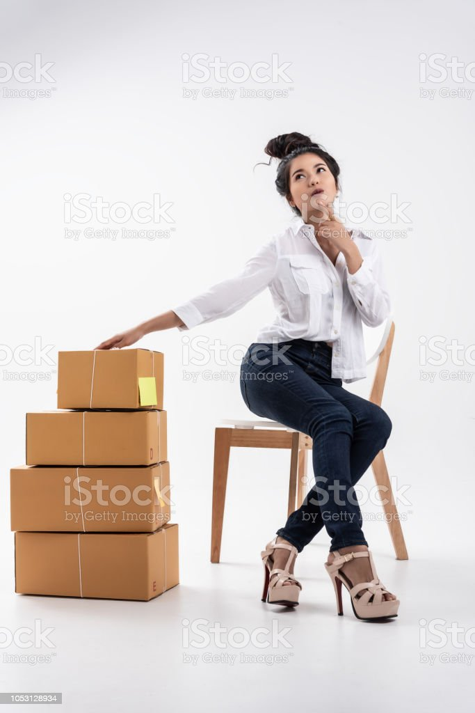 In business on line,Young beutiful entrepreneur woman,teenager business owner work and use laptop and phone call receive frome customer,take note and prepair to send product by mail. stock photo
