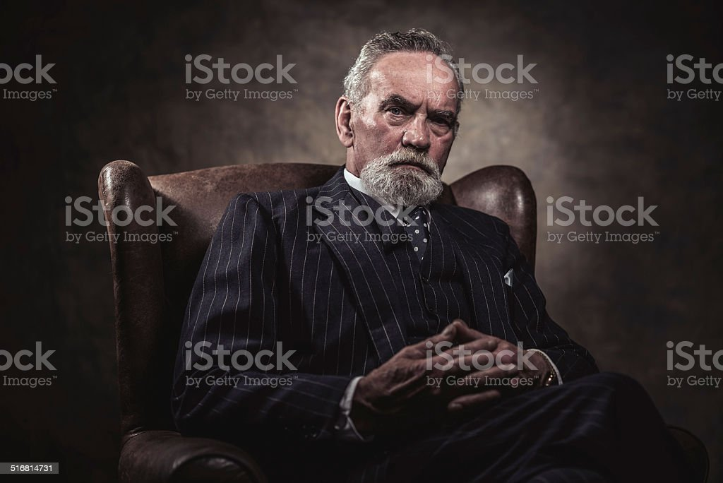 In chair sitting characteristic senior business man. Gray hair. stock photo