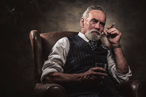 in chair sitting senior business man with cigar and whisky. - guy with cigar stockfoto's en -beelden