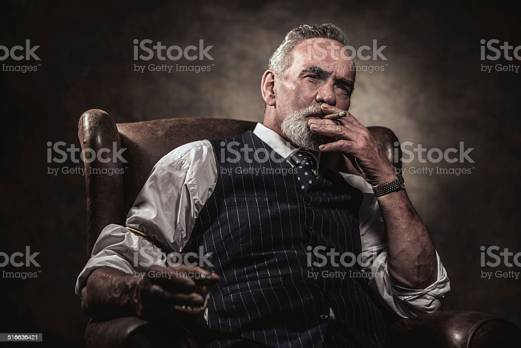 In chair sitting senior business man with cigar and whisky. stock photo