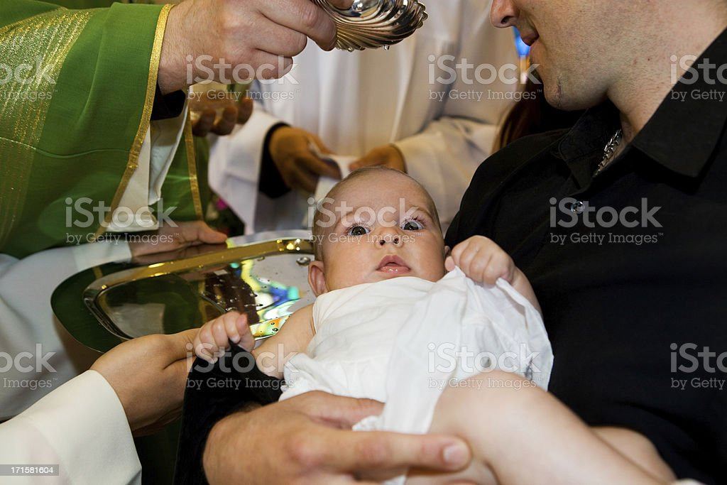 In church...Priest is baptizing little baby. stock photo