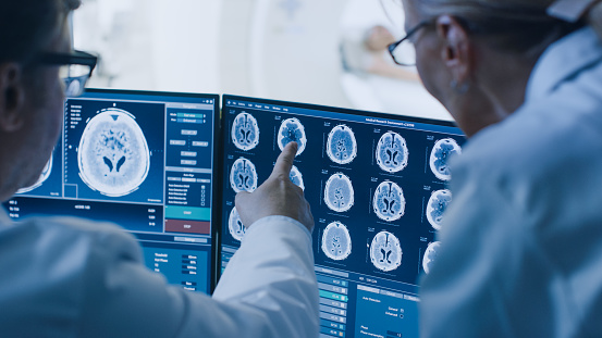 istock In Control Room Doctor and Radiologist Discuss Diagnosis while Watching Procedure and Monitors Showing Brain Scans Results, In the Background Patient Undergoes MRI or CT Scan Procedure. 1074166486