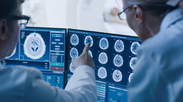 in control room doctor and radiologist discuss diagnosis while watching procedure and monitors showing brain scans results, in the background patient undergoes mri or ct scan procedure. - medical x ray stock pictures, royalty-free photos & images
