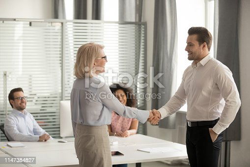 924519152 istock photo In coworking middle aged boss greeting new employee with handshake 1147384827