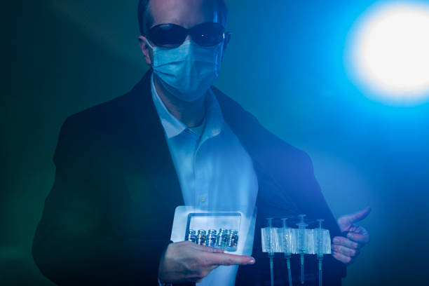 In dark moody atmosphere, a dealer wearing facial mask and sunglasses selling fake illegal COVID-19 Vaccines hidden in the inner pocket of his suit stock photo