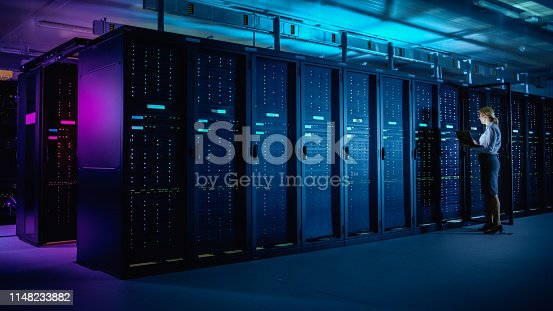 In Data Center: IT Technician Running Maintenance Programme on Laptop, Controls Operational Server Rack Optimal Functioning. Modern High-Tech Telecommunications Operational Data Center in Neon Lights.