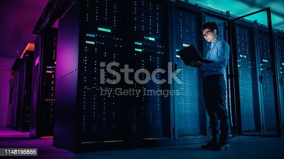 In Data Center: Male IT Technician Running Maintenance Programme on a Laptop, Controls Operational Server Rack Optimal Functioning. Modern High-Tech Operational Super Computer in Neon Colours, Lights
