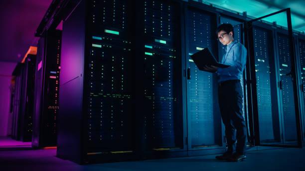 в центре обработки данных: мужской ит-техник работает программа технического обслуживания на ноутбуке, контролирует операционную стойку с - технологии стоковые фото и изображения