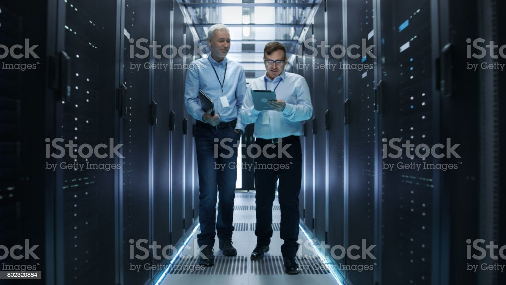 In Data Center Two IT Engineers Walking Through Rows of Server Racks. They Work on Tablet Computer and Laptop. stock photo