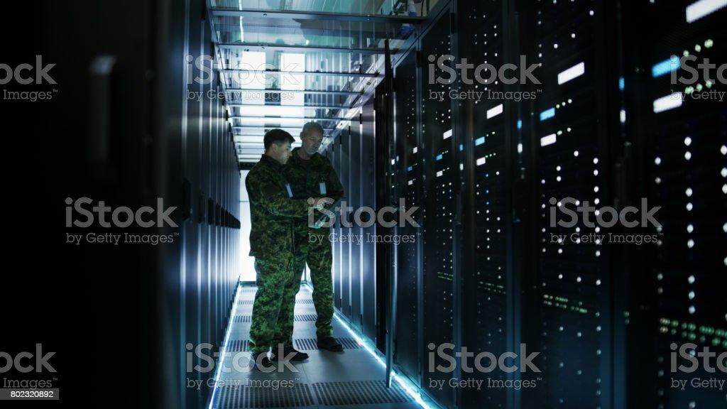 Datacenter deux hommes militaires travaillent avec armoire Rack Open Server. Détient un militaire Edition portable. - Photo