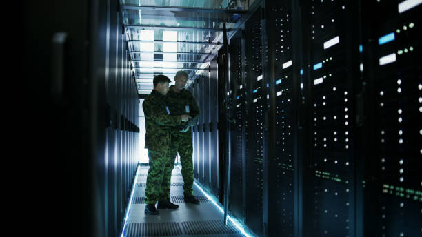 In Data Center Two Military Men Work with Open Server Rack Cabinet. One Holds Military Edition Laptop. In Data Center Two Military Men Work with Open Server Rack Cabinet. One Holds Military Edition Laptop. defend stock pictures, royalty-free photos & images