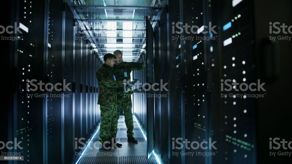 In Data Center Two Military Men Work with Open Server Rack Cabinet. One Holds Military Edition Laptop. stock photo