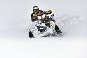 In deep snowdrift snowmobile rider make fast turn