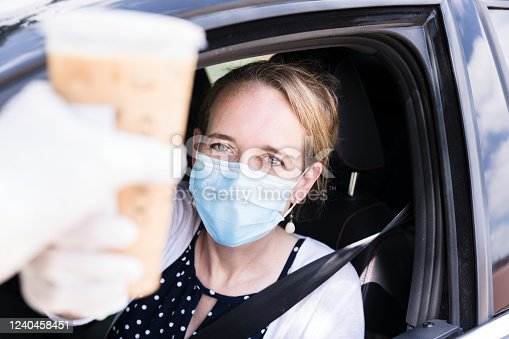 The mid adult woman purchases hot coffeee in a drive-through restaurant.  Both the woman and the person handing her the coffee wear protective gloves.  The woman is also wearing a protective mask.