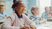 istock In Elementary School Class: Portrait of a Brilliant Black Girl with Braces Writes in Exercise Notebook, Smiles. Junior Classroom with Diverse Group of Children Learning New Stuff 1253508097