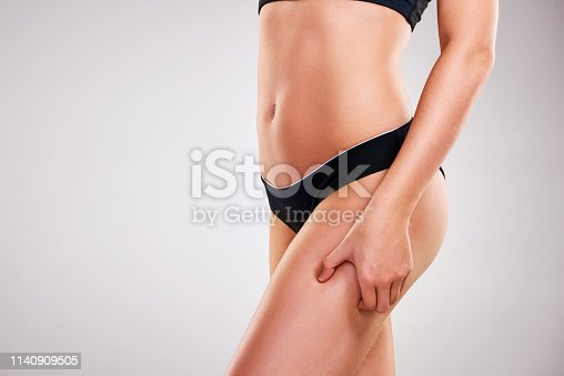 Cropped studio shot of a fit young woman pinching her thigh against a grey background