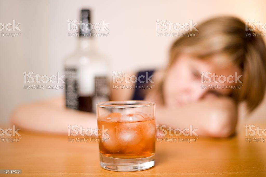 In focus glass of alcohol with blurry woman in background stock photo