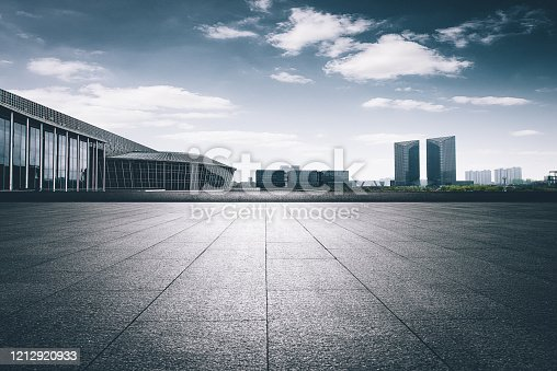 In front of the modern buildings in the city, there is a wide and empty marble square with high contrast of blue and nostalgia