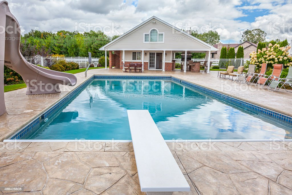 In Ground Swimming Pool with Pool-House, Slide, Diving Board. stock photo