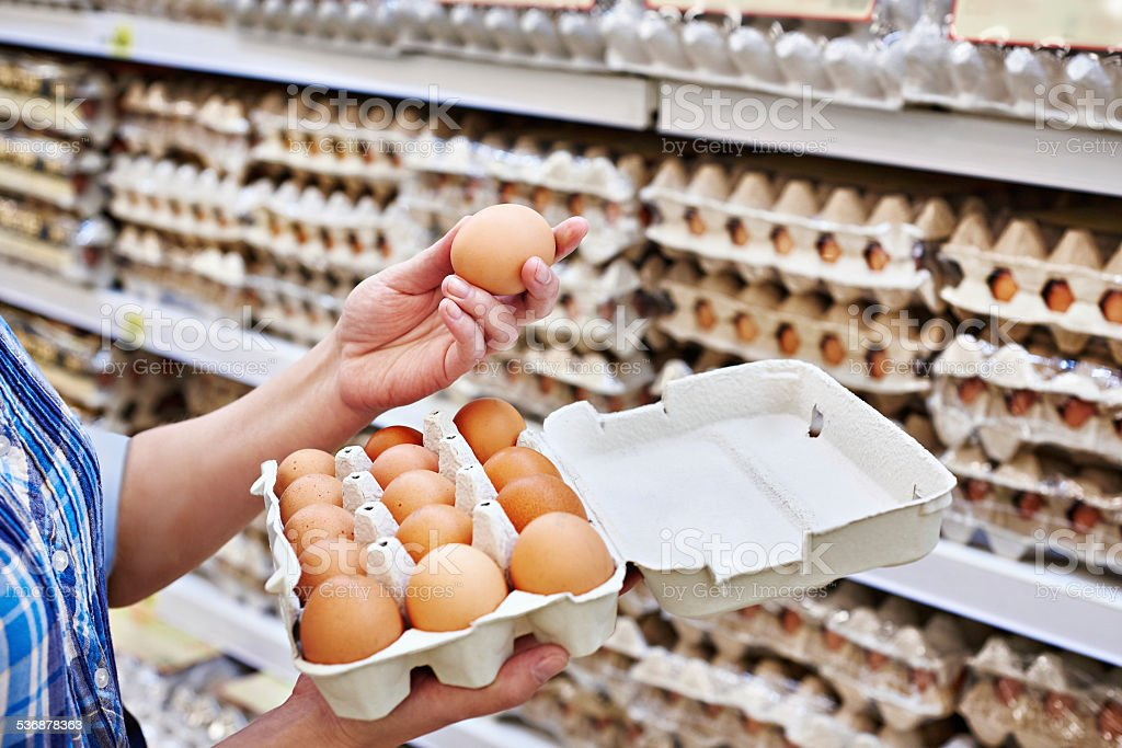 In hands of woman packing eggs in supermarket stock photo