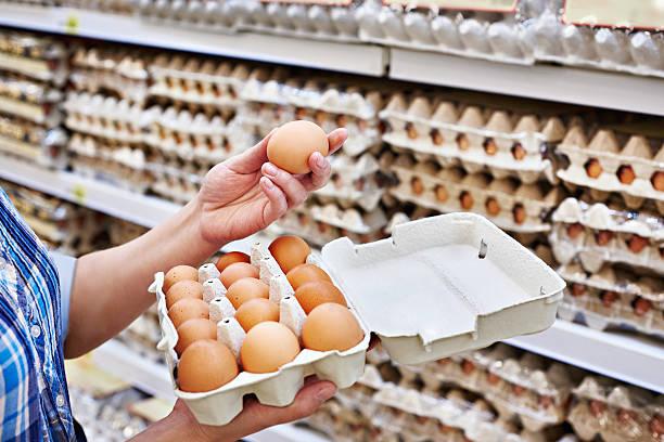 nelle mani di donna imballaggio uova in supermercato - icona supermercato foto e immagini stock