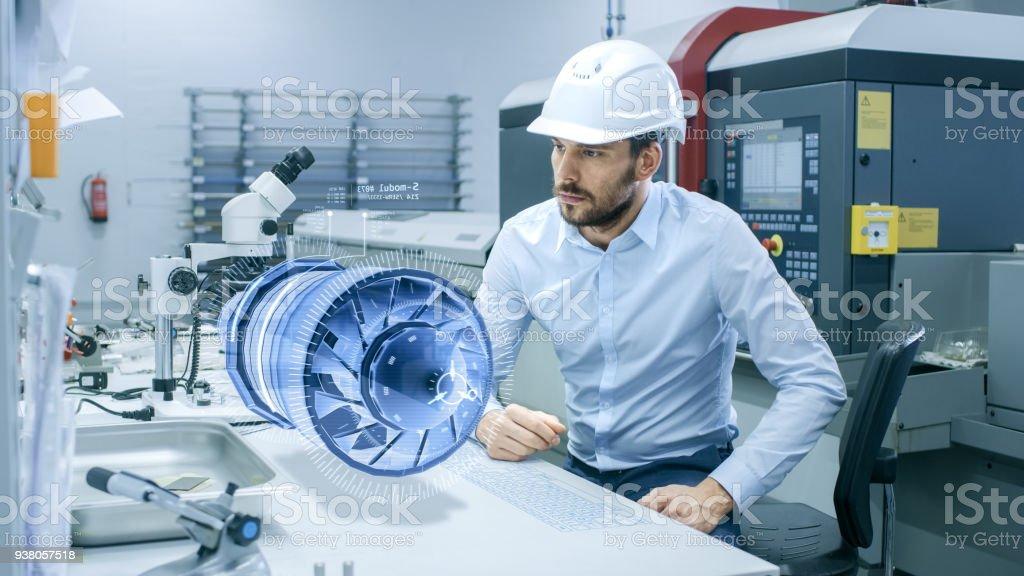 En alta tecnología futurista fábrica jefe ingeniero trabaja con proyección holográfica 3D modelo del prototipo de turbina del motor. Futurista diseño de aplicaciones de realidad Virtual mixta. - Foto de stock de Adulto libre de derechos