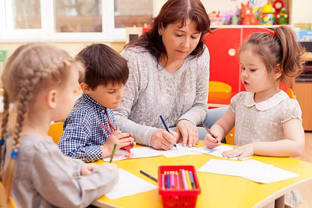 in bereits im kindergarten zeichnung-unterricht - erzieherin stock-fotos und bilder