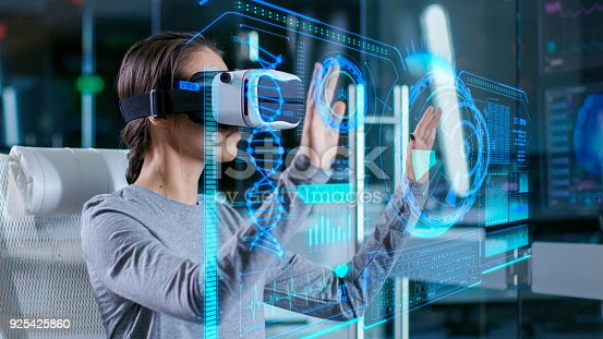 851956150istockphoto In Laboratory Scientist Wearing Virtual Reality Headset Sitting in a Chair Interacts with Futuristic Holografic Interface, Showing Neurological Data. Modern Brain Study/ Neurological Research Center. 925425860