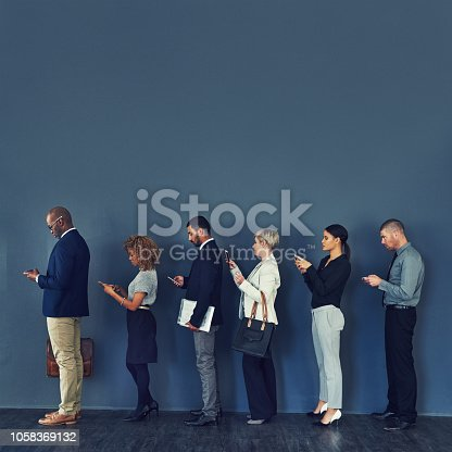 Studio shot of a group of businesspeople using wireless devices while waiting in line