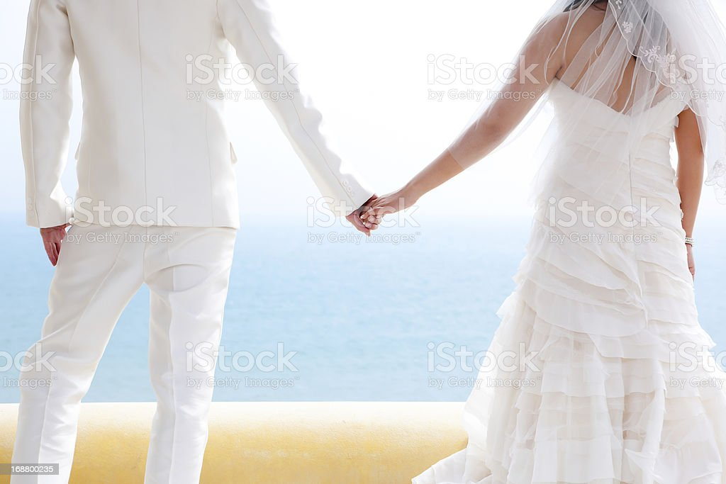 In love bride and groom are holding each other's hands royalty-free stock photo