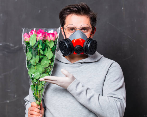 in love man in face mask holds roses bouquet stock photo