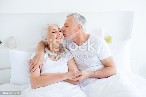 istock In love, sweet , grandma, granddad couple people with gray hair hug each other and in comfortable bright interior room. Man gently kisses his wife on the cheek with closed eyes 1049791736