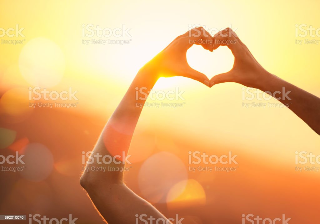 In love with the landscape Shot of an unidentifiable woman's hands making a heart shape over a sunset landscape Adult Stock Photo