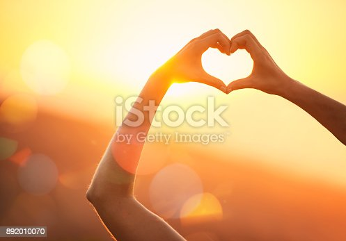 Shot of an unidentifiable woman's hands making a heart shape over a sunset landscape