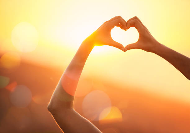 In love with the landscape Shot of an unidentifiable woman's hands making a heart shape over a sunset landscape amor stock pictures, royalty-free photos & images