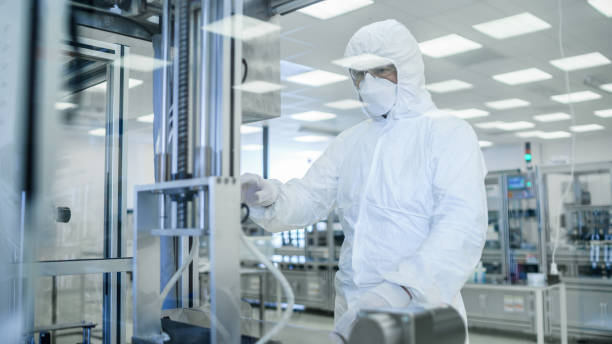 In Manufacturing Facility Shot of Scientist in Sterile Protective Clothing Work on a Modern Industrial 3D Printing Machinery. Pharmaceutical, Biotechnological Manufacturing Process. Shot from Inside. stock photo