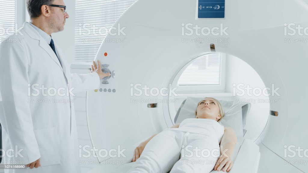 In Medical Laboratory Radiologist Controls MRI or CT or PET Scan with...
