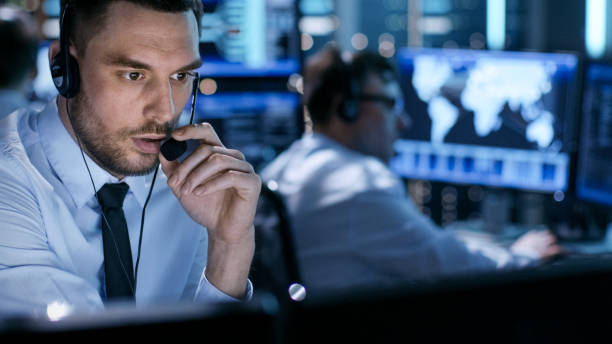 In Monitoring Room Technical Support Specialist Speaks into Headset. His Colleagues are Working in the Background. stock photo