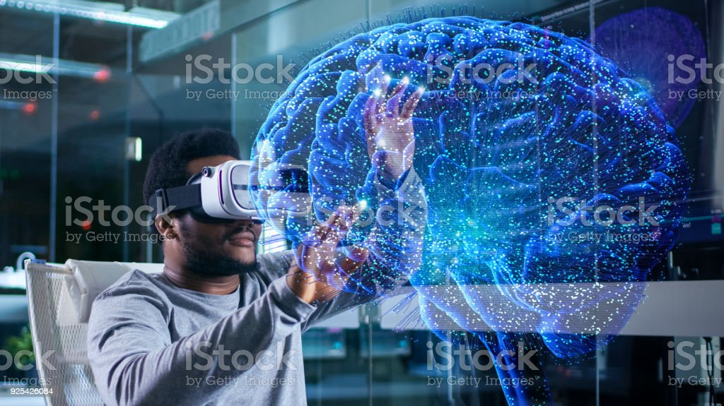 In Near Future Laboratory Scientist Wearing Virtual Reality Headset Sitting in a Chair Using Futuristic Holografic Interface. Modern Brain Study/ Neurological Research Center. stock photo