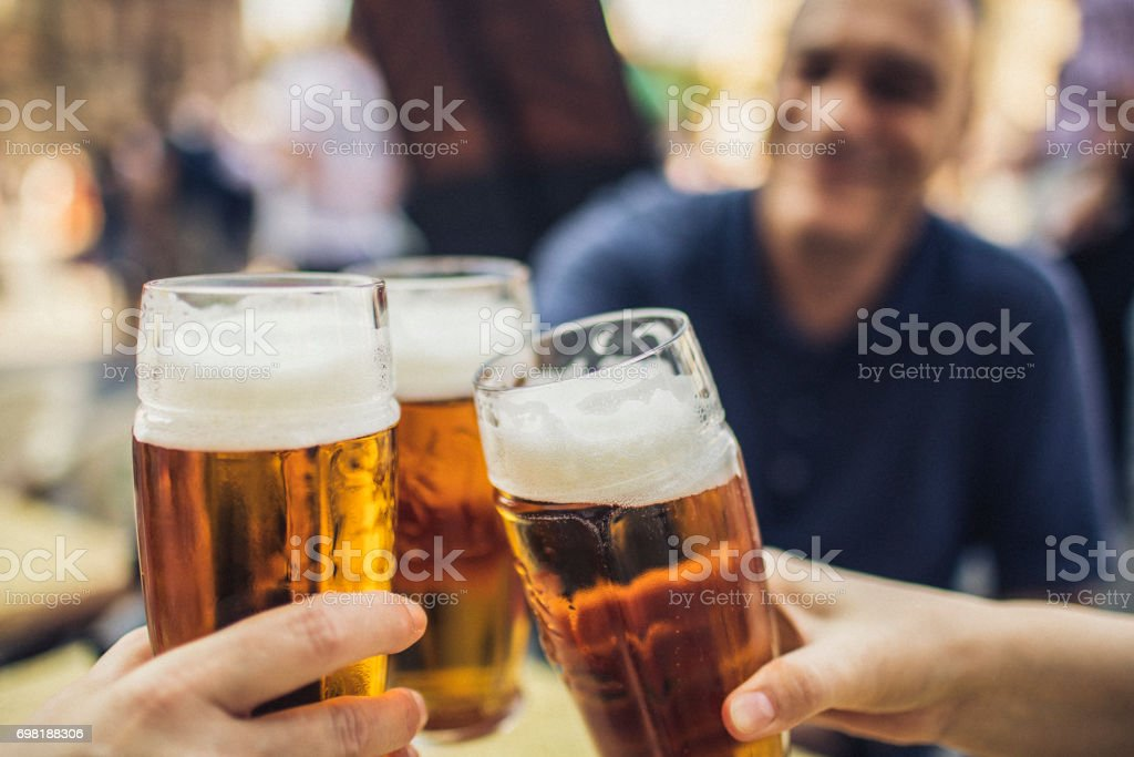 In Prague, three friends cheering on good news with glasses of pilsner beer. stock photo