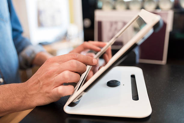 In restaurant the waiter prepares the bill on tablet pc stock photo
