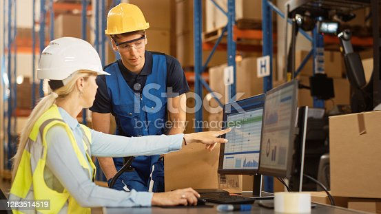 In Retail Warehouse Manager Uses Computer with Inventory Checking Software, Talks with Storehouse Worker about Package Delivery. International Distribution Center with Shelves Full of Products