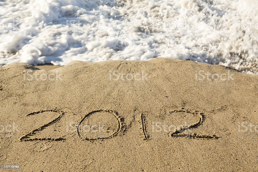 2012 in sand being covered by sea waves royalty-free stock photo