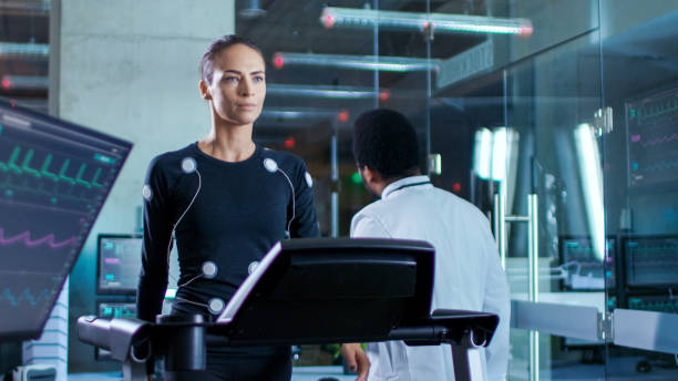 In Scientific Sports Laboratory Beautiful Woman Athlete Walks on a Treadmill with Electrodes Attached to Her Body, While Black Scientist Going Away, Monitors Show EKG Data on Display. stock photo