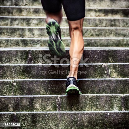 Close up of man with muscular legs running up a flight of stairs in old European city.
