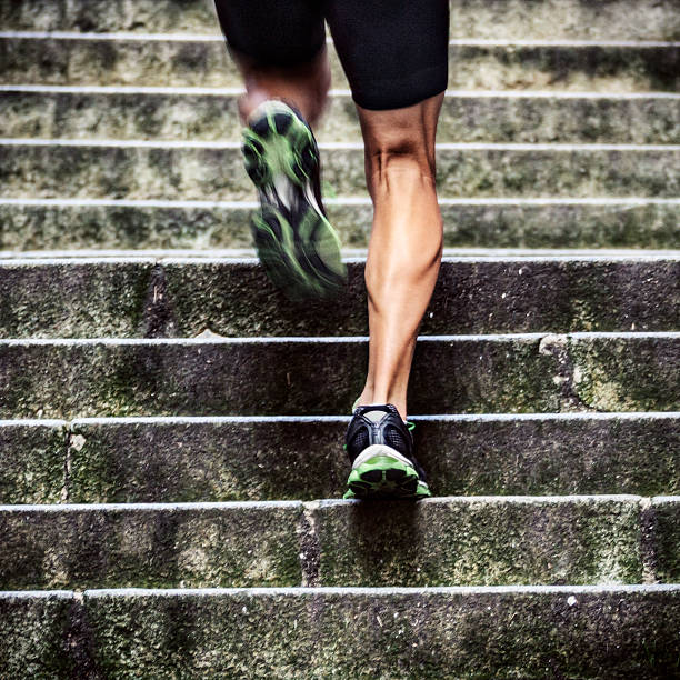 In Shape Close up of man with muscular legs running up a flight of stairs in old European city. davelongmedia stock pictures, royalty-free photos & images