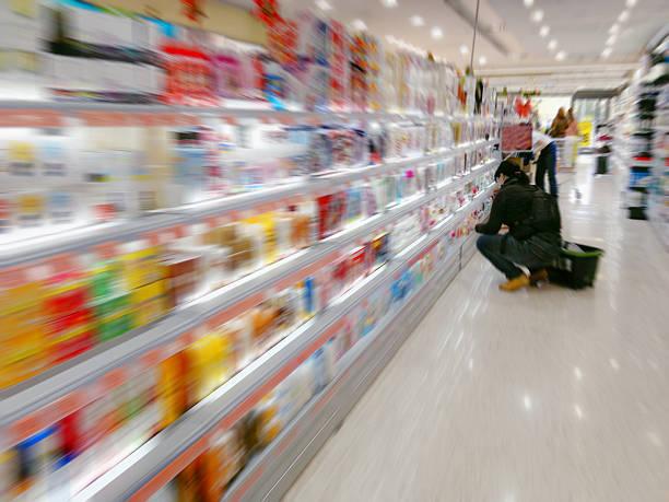 im supermarkt an einem regal mit farbenfrohen waren - drogerie stock-fotos und bilder