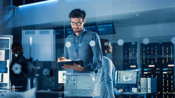 In Technology Research Facility: Chief Engineer Stands in the Middle of the Lab and Uses Tablet Computer. Team of Industrial Engineers, Developers Work on Engine Design Use Digital Whiteboard and Computers stock photo