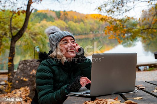 istock In the autumn season, the woman who is taking a stroll in the forest use a computer in the lake view. 1286591889