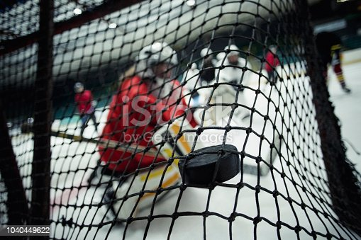 Rear view of a ice hockey net with a puck hitting the back of the net. The focus is on the foreground on the puck, scoring a goal.